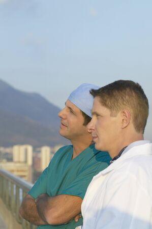 scrub cap: Two male doctors on balcony