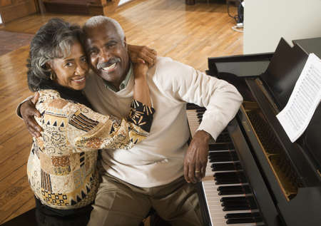 boomers: Senior African couple hugging next to piano