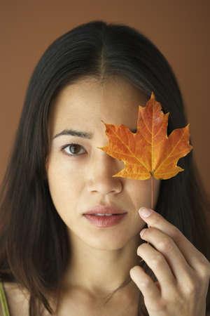 gratifying: Asian woman holding autumn leaf over eye LANG_EVOIMAGES