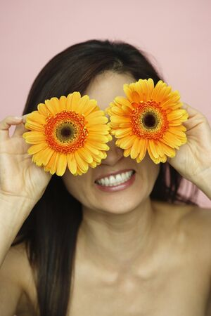 spiritualism: Asian woman holding flowers over eyes
