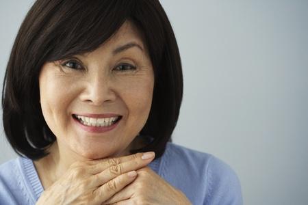 mujeres sentadas: Mujer asiática mayor que se reclina la barbilla en las manos
