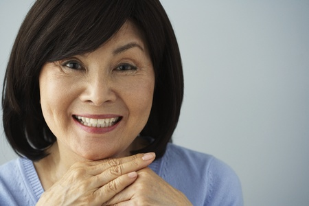 woman close up: Senior Asian woman resting chin on hands LANG_EVOIMAGES