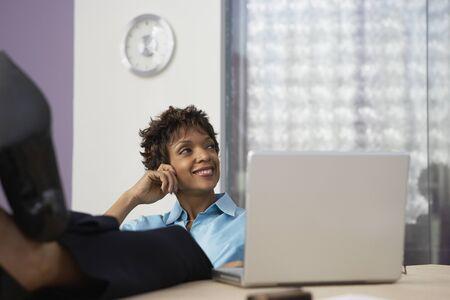 visualizing: African businesswoman resting feet on desk LANG_EVOIMAGES