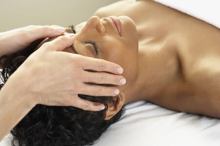 African woman receiving facial massage Stock Photo