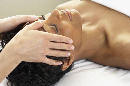 Receiving: African woman receiving facial massage LANG_EVOIMAGES