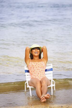lighthearted: Asian woman sitting in beach chair