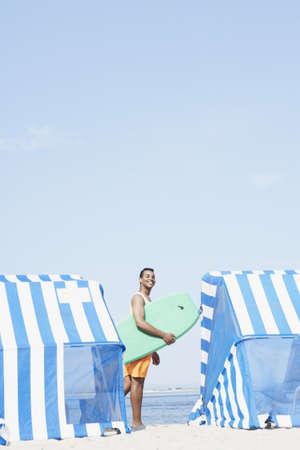 boogie: Hispanic man holding boogie board at beach