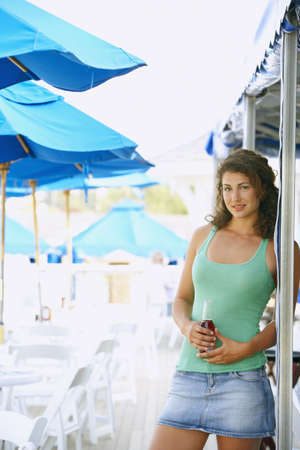 unconcerned: Young woman with drink at beach