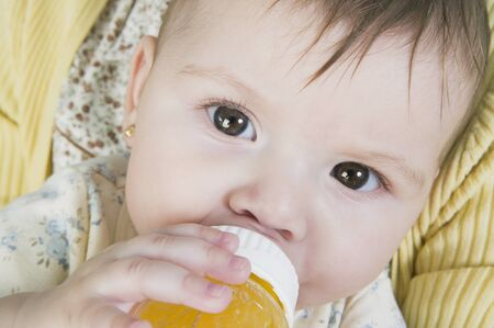 playing on divan: Hispanic baby drinking from bottle
