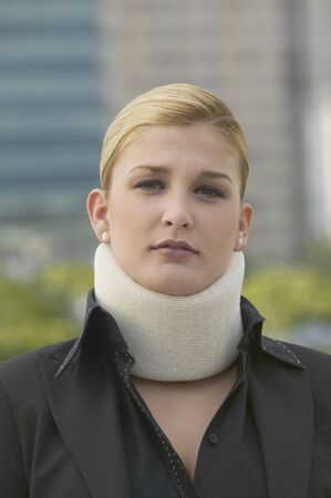 Hispanic businesswoman wearing neck brace