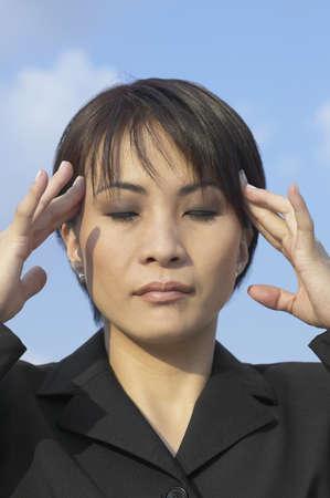eyes downcast: Asian businesswoman rubbing temples