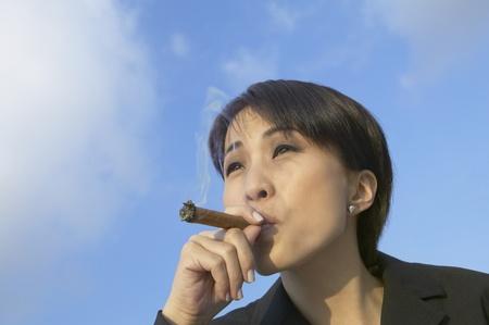 Asian businesswoman smoking cigar