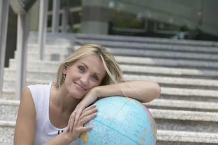 connexion: Young woman leaning on globe LANG_EVOIMAGES
