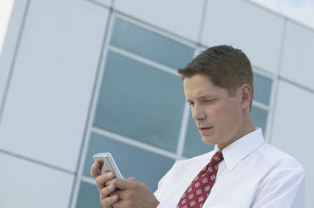Businessman dialing cell phone Stock Photo