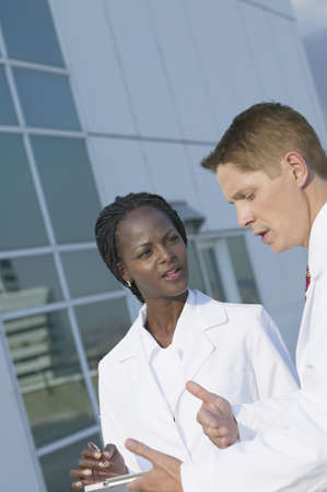 Two medical professionals discussing chart