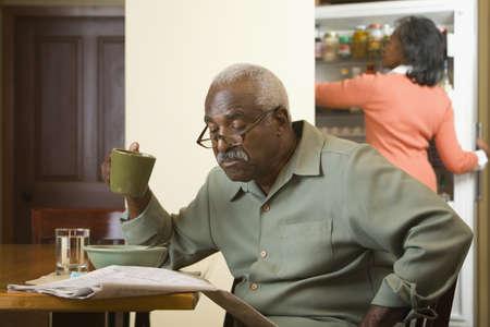 babyboomer: Senior African man reading newspaper LANG_EVOIMAGES