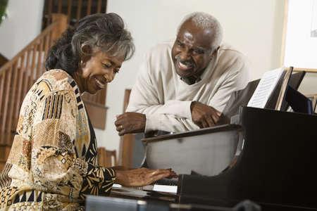 babyboomer: Senior African woman playing piano LANG_EVOIMAGES