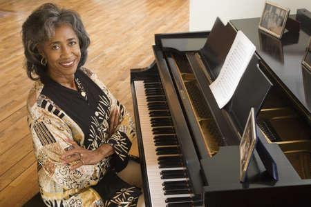babyboomer: Senior African woman sitting at piano