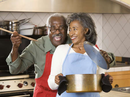 babyboomer: Senior African couple cooking LANG_EVOIMAGES
