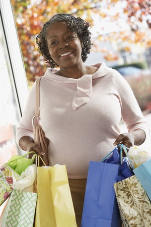 shopping buddies: Senior African woman carrying shopping bags