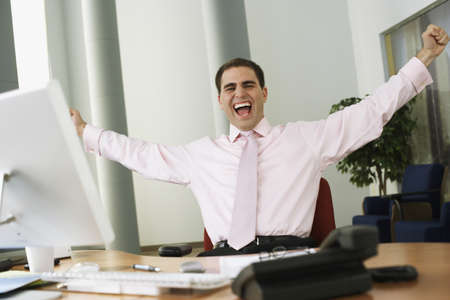 two persons only: Middle Eastern businessman cheering at desk