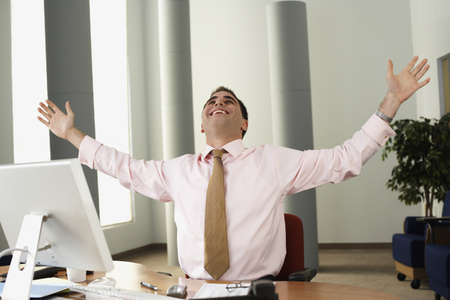 middle eastern: Middle Eastern businessman cheering at desk