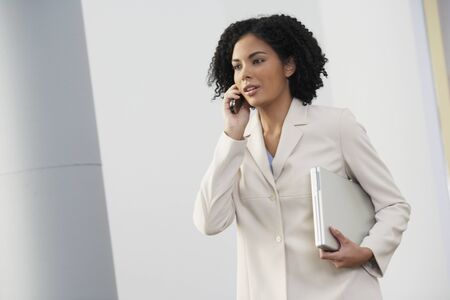 connexion: African businesswoman talking on cell phone