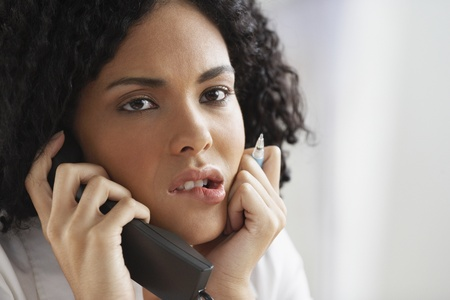 solemn: African businesswoman talking on telephone