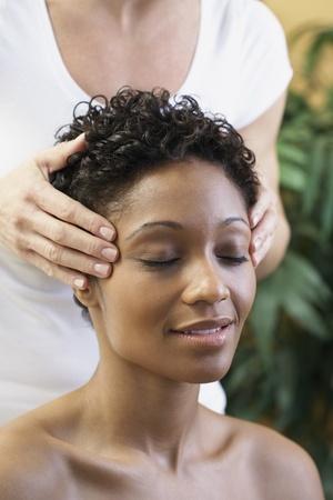 relishing: African woman receiving facial massage LANG_EVOIMAGES