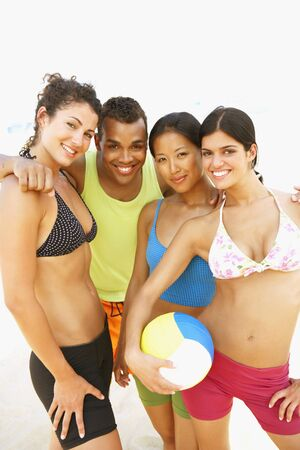 bathingsuit: Multi-ethnic friends holding volleyball