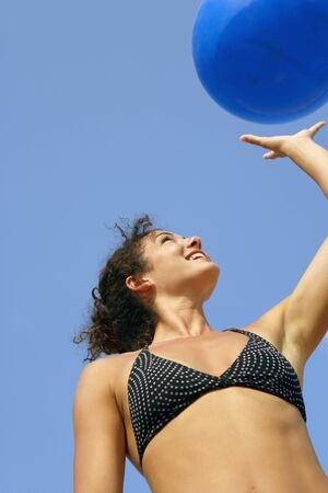 bathingsuit: Young woman holding beach ball
