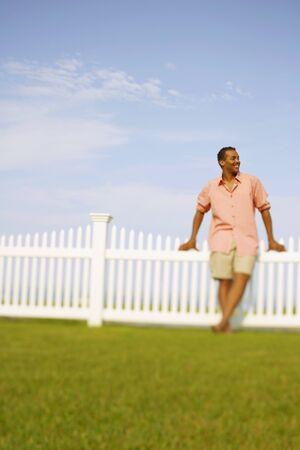 slumbering: Hispanic man leaning on fence