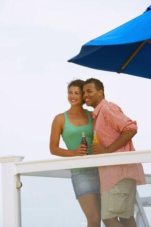 mischeif: Couple having drinks on balcony
