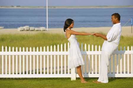 leaning by barrier: Couple holding hands at beach LANG_EVOIMAGES