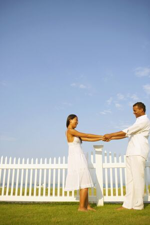 leaning by barrier: Couple holding hands next to fence