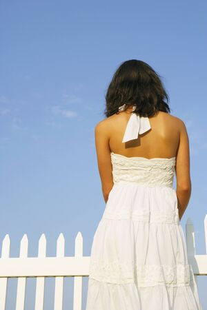 leaning by barrier: Rear view of woman next to fence