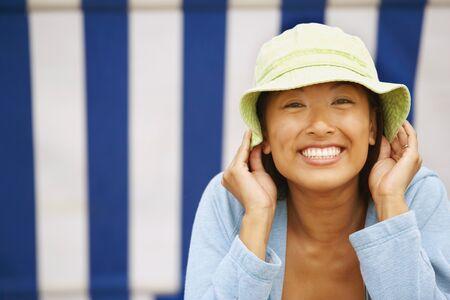 relishing: Asian woman wearing sun hat LANG_EVOIMAGES