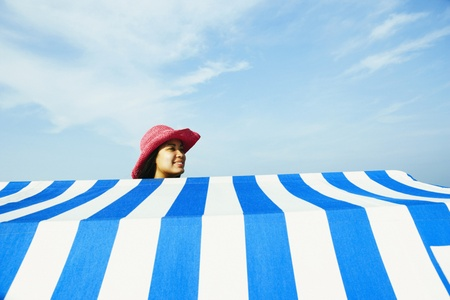 the sun and shade: Hispanic woman standing behind beach sun shade LANG_EVOIMAGES