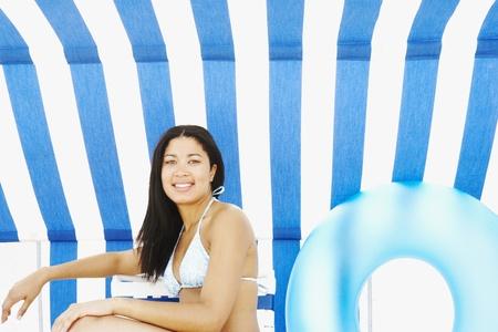 attired: Hispanic woman sitting under beach sun shade LANG_EVOIMAGES