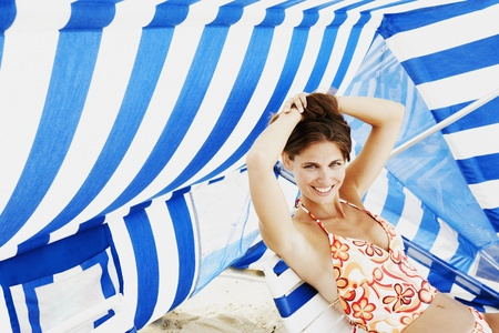 the sun and shade: Young woman sitting under beach sun shade