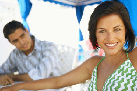 wooing: Young woman smiling with man in background LANG_EVOIMAGES