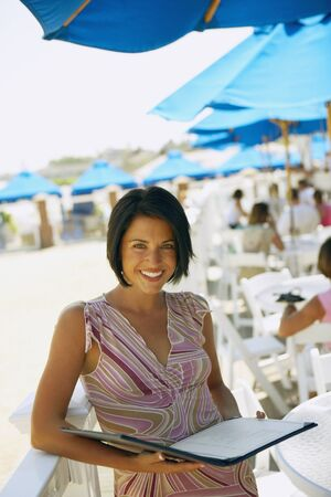 Woman holding menu at beach restaurant
