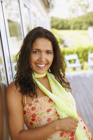 Hispanic woman leaning against glass door Stock Photo