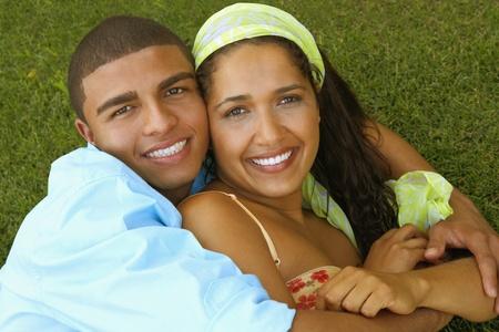 Hispanic couple hugging in grass