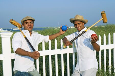 longshot: Hispanic twin brothers holding croquet mallets