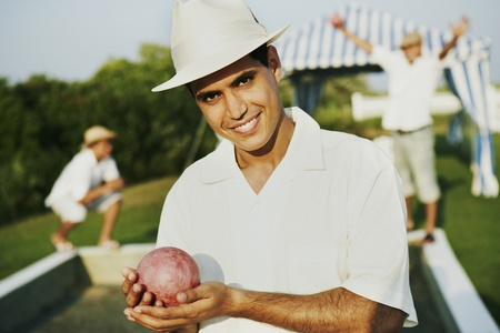 leaning by barrier: Egyptian man holding ball