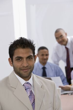 scrub cap: Indian businessman with co-workers in background LANG_EVOIMAGES