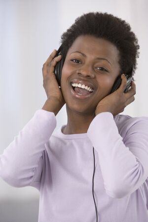 African woman listening to headphones