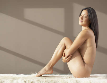 asian and indian ethnicities: Nude Asian woman pulling knees up to chest