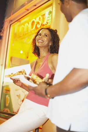 flogging: African couple eating pizza on sidewalk LANG_EVOIMAGES